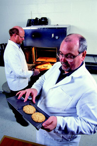 Cookie-baking test reveals whether wheat has the desired characteristics to make tender pastry products. Here, food technologist Ron Martin (left) removes test cookies from the oven while food technologist Charles Gaines measures two cookies.