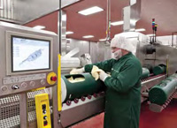 Operator loads product in flexible packaging into the high-presssure processing system at Sandridge Food.