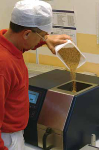 Technician adds a wheat sample to Foss's Infratec 1241 Grain Analyzer. The instrument includes ready-to-use calibrations for protein, moisture, starch, and oil in corn, soybeans, and rice and requires no sample preparation.