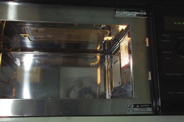 Fig.1—Interior of a combination microwave–infrared oven (AdvantiumTM from General Electric, Louisville, Ky). The inside of the oven has dimensions 0.470 m x 0.356 m x 0.215 m (height). The infrared (halogen) sources are at the top (as shown in the middle) and at the bottom (not shown). The microwaves are introduced from the side as shown.