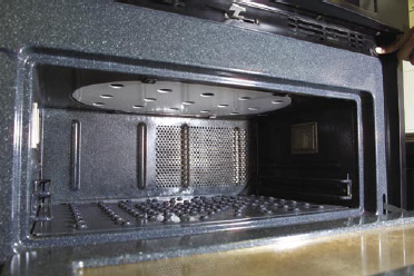 Fig. 2—Interior of a combination microwave–jet-impingement oven (Thermador JetDirect oven, model CJ302UB, technology licensed from Enersyst Development Center, Dallas, Tex.). The inside of the oven has dimensions 0.61 m x 0.375 m x 0.235 m (height). The microwaves are introduced from the top, and the air jets are introduced from both the top and the bottom.