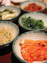 Side dishes served at a Korean BBQ dinner include various vegetables as well as kimchi (front), which is a dish of fermented vegetables (in this case cabbage) and seasonings.