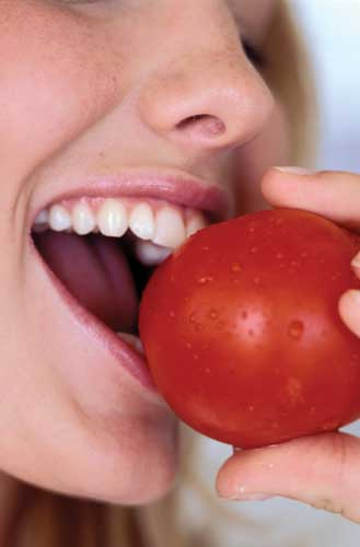Woman eating a tomato.