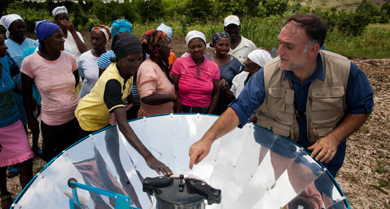 Jose Andres demonstrates how to use a solar cookstove in Haiti